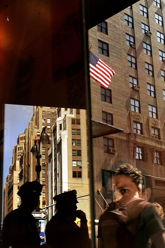 "9/1/2004 -- New York, NY -- Security presence -- Fraser Nelson, the poltiical editor for the Scotsman Newspaper, watches out of the window of a Starbucks on 8th Avenue near Madison Square Garden. Police stood guard on nearly every corner to secure the vicinity of the Republican National Convention. Nelson said, ""[The police] have been very effective. If you look at the potential dangers, things have gone pretty well. They've been able to combine overwhelming numbers with a really relaxed manner."""