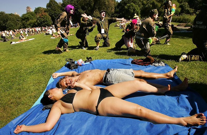 """8/29/2004 -- New York, NY -- Protesting the RNC in NYC -- Sunbathers Lily Phan and Glen Reppy laugh as their peaceful Sunday afternoon in Central Park becomes the staging grounds for political street theater. The Clandestine Insurgent Rebel Clown Army, or CIRCA, held an impromtu revival service with a puppet doll of George Bush as the prohet. Here, they are seen racing over the lawn past the sunbathers. Lily said, """"We came to Central Park to get away from [the protests]. They came to us."""" She does no plan to vote this year. Glen is undecided as to for whom he will vote. He said, """"Both parties are moving toward the ends of the spectrum, not toward the middle."""" During the day, hundreds of thousands (???) of peaceful protesters streamed through the streets of New York of a hot Sunday morning. As of 4 pm, protesters were still marching past the starting point of the parade. Photo by Dina Rudick, The Boston Globe."""
