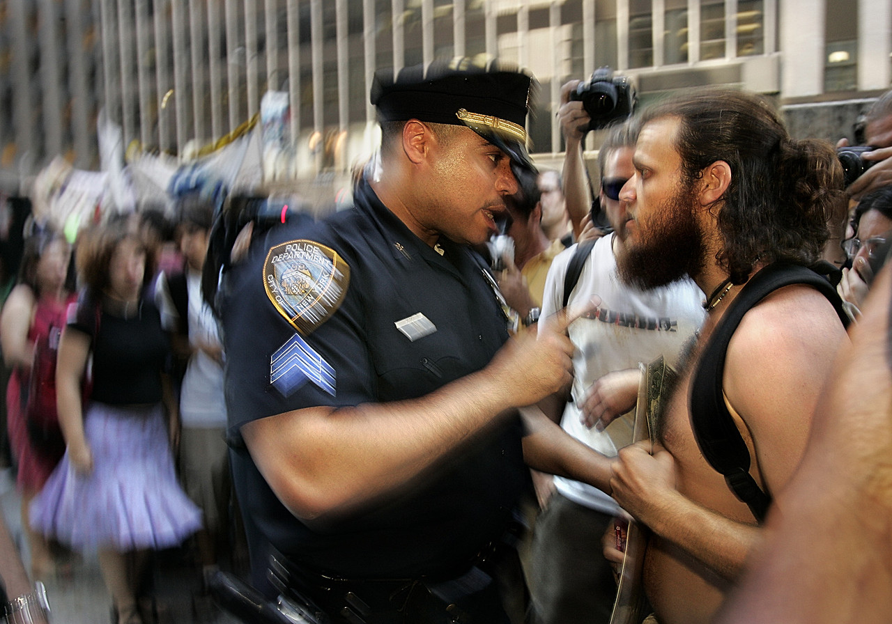 8/31/2004 -- New York, NY -- Police broke up a large protest in front of the FOX News headquarters in Manhattan. In this picture, a policeman pushes a protester that is slow to move and is questioning why he must move in the first place. Photo by Dina Rudick, The Boston Globe.