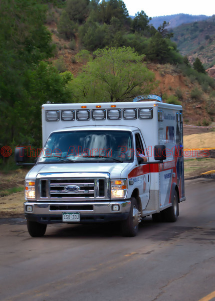 An El Paso County-American Medical Response Ambulance, coming away from the pileup of vehicles on US Highway 24, in Manitou Springs, Colorado. Thankfully, no injuries were reported from these accidents on the flooded roadway.