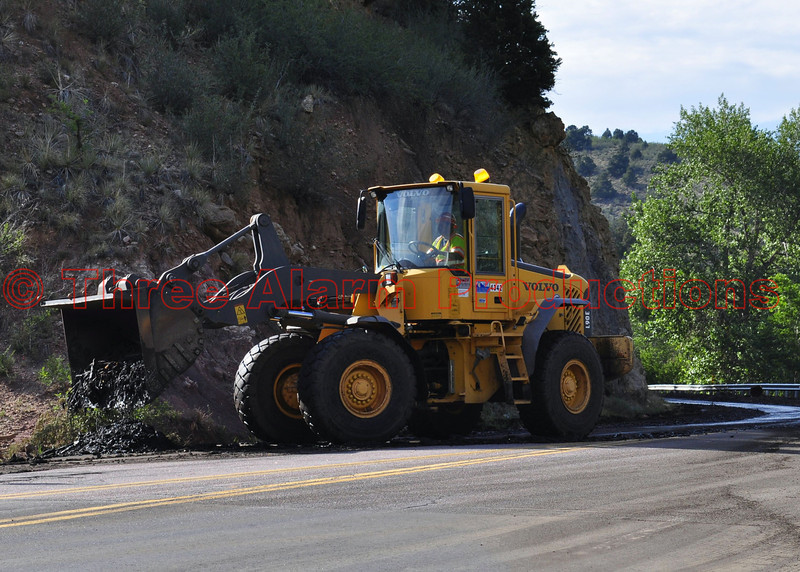 Heavy equipment working on mud and debris removal on Manitou Avenue in Manitou Springs, Colorado.