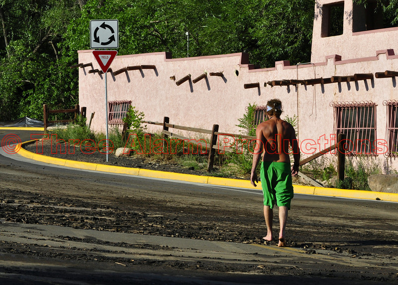A Manitou Springs Resident walking over debris that washed onto the roadway from the Waldo Canyon Burn Scar in Colorado.
