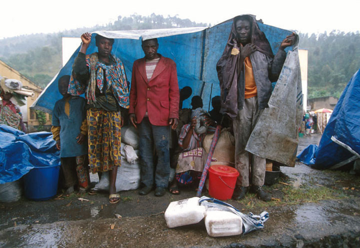 "UNHCR and the NGO distribute the ""sheetings"", blue plastic sheets.<br /> Rwanda, November 1996.<br /> <br /> © Laura Razzano"