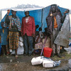"UNHCR and the NGO distribute the ""sheetings"", blue plastic sheets.<br /> Rwanda, November 1996.<br /> <br /> © Laura Razzano"