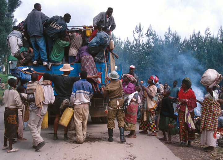 A soldier hits some refugees that want to find place on wagon. <br /> Rwanda, November 1996.<br /> <br /> © Laura Razzano
