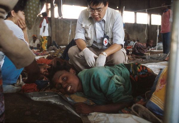 In a cowshed after the borderline between Zaire and Rwanda is made ready the first aid post. A doctor of the International Red Cross tries to save a refugee.<br /> Rwanda, November 1996.<br /> © Laura Razzano