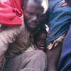 A father and his child try to get on a wagon.<br /> Rwanda, November 1996.<br /> <br /> © Laura Razzano