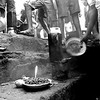 A few prisoners cook some beans with small canned tins and live coals.<br /> Rwanda, Prison of Gitarama, November 1996.<br /> © Laura Razzano