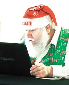 Ron Cattrell, Santa treasurer, looks at his laptop during a meeting of the Buckeye Santas club. BRUCE BISHOP/CHRONICLE