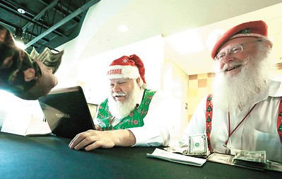 Santa treasurer Ron Cattrell, left, checks in Santas at a business meeting, receiving help from Dan Cunningham, right, of Elyria. BRUCE BISHOP/CHRONICLE