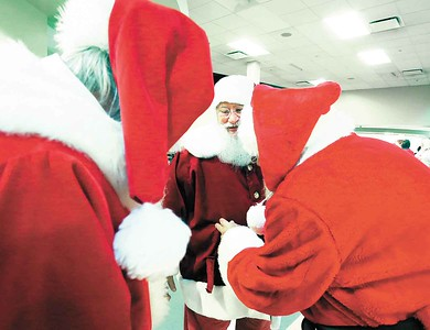 Tom Shilling gets some help as the Santas prepare for a group shot at Buckeye Santa School. BRUCE BISHOP/CHRONICLE