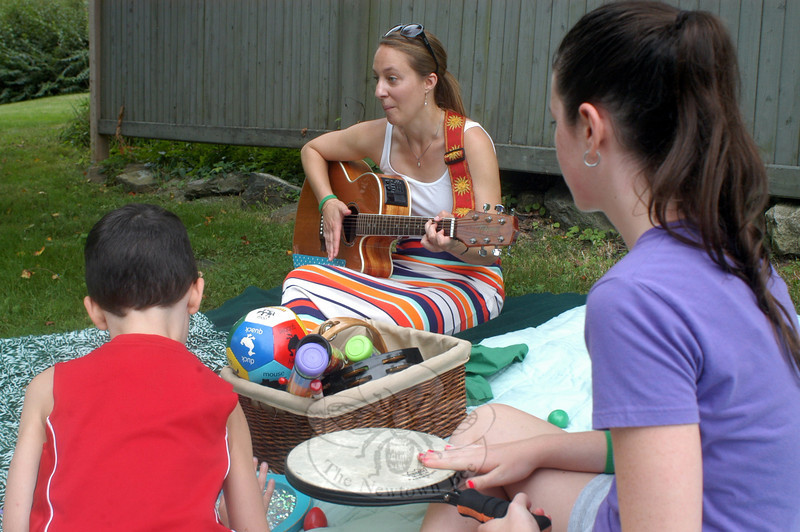 Emily Bevelaqua of Connecticut Music Therapy Services strums the guitar as Joshua and Kelsey Heyel play along at the ice cream social at Trinity Episcopal Church on August 31. (Hutchison photo)