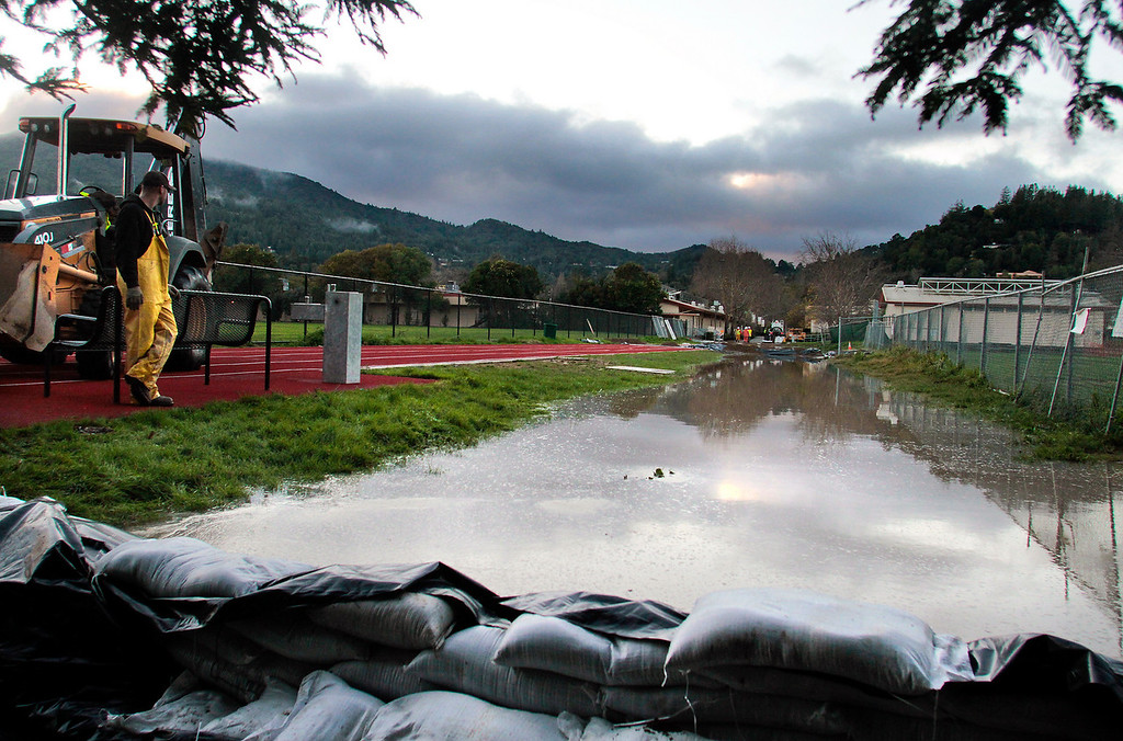 A worker from the Ross Valley Sanitation District looks over a raw sewage spill behind Kent Middle School in Kentfield, Calif., on Wednesday December 22,  2010. The sand bags are trying to prevent the sewage from entering the creek.