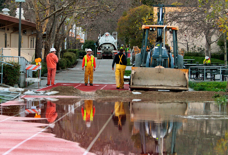 Workers from the Ross Valley Sanitation District work on cleaning up a raw sewage spill behind Kent Middle School in Kentfield, Calif., on Wednesday December 22,  2010.