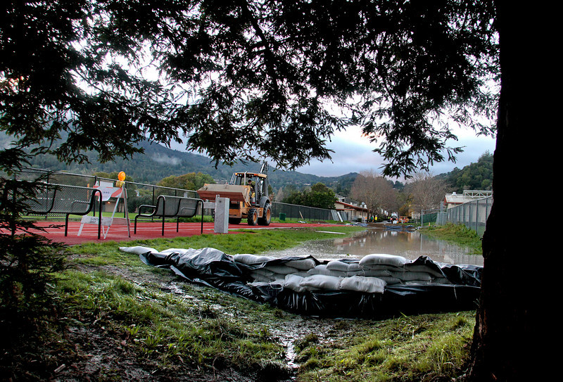 Workers from the Ross Valley Sanitation District created a dam with sand bags to prevent raw sewage from entering the creek behind Kent Middle School in Kentfield, Calif., on Wednesday December 22,  2010.