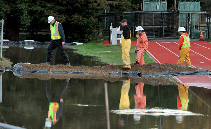 Workers from the Ross Valley Sanitation District view the raw sewage spill behind Kent Middle School in Kentfield, Calif., on Wednesday December 22,  2010.