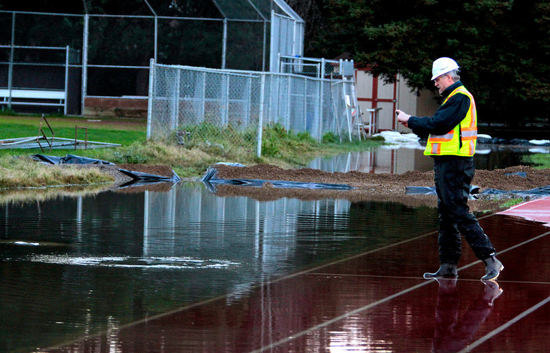 A worker from the Ross Valley Sanitation District takes a picture of the raw sewage spill behind Kent Middle School in Kentfield, Calif., on Wednesday December 22,  2010.