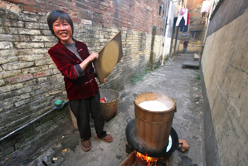 A local woman shows off her rice cooker in the hutong.