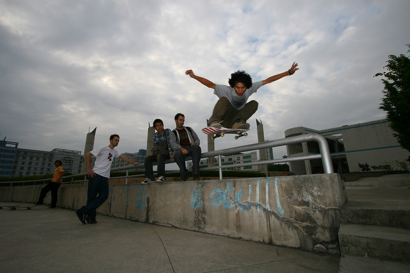 Thrasher Fu ollies over the rail at the Xili University Skatepark in Shenzhen as friends look on. <br /> <br /> November 7, 2007 © Jesse Warren