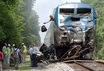 A backpack is tossed from the mangled and charred locomotive of the Amtrack train, the City of New Orleans, following a collision with a garbage truck north of Crystal Springs in Copiah County Tuesday afternoon.