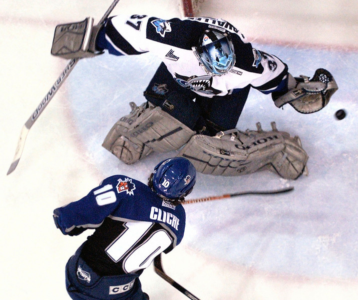 Lewiston has the only American team in the QMJHL.  Rimouski goalie Guillaume Lavalle flashes his glove to rob Lewiston Maineiacs Marc-Andre Cliche of a goal.