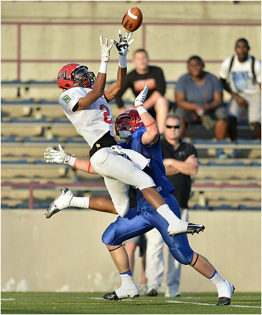 Erie City's Dajhere Pacley leaps in front of Erie County opponent Brian McNally to make a catch near the end zone during the second quarter of the 76th annual City-County Save-An-Eye All-Stars football game at Veteran's Stadium in Erie, Pa. on Friday, July 25, 2014. The County squad won 21-14.