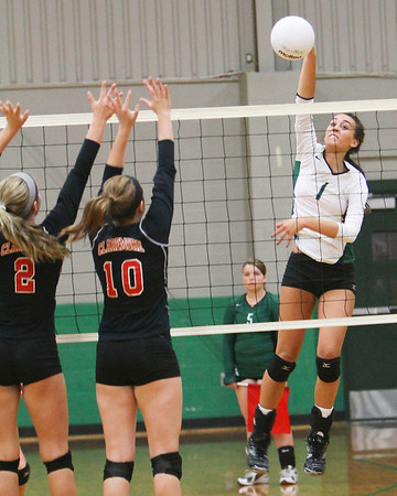 Muskogee's Claire Farmer, right, goes up for a kill past Claremore's Breanna Kimblern, left, and Allison Howell during Thursday's match. The Lady Roughers improved to 8-2 with a 3-0 win over the Lady Zebras.