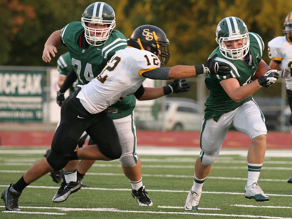 Muskogee's Jefferson Moore, right, gets a block from J.B. Clark, left, springing him past Sand Springs' Riley Askew during Friday's season opener at Indian Bowl. The Roughers lost 40-28.
