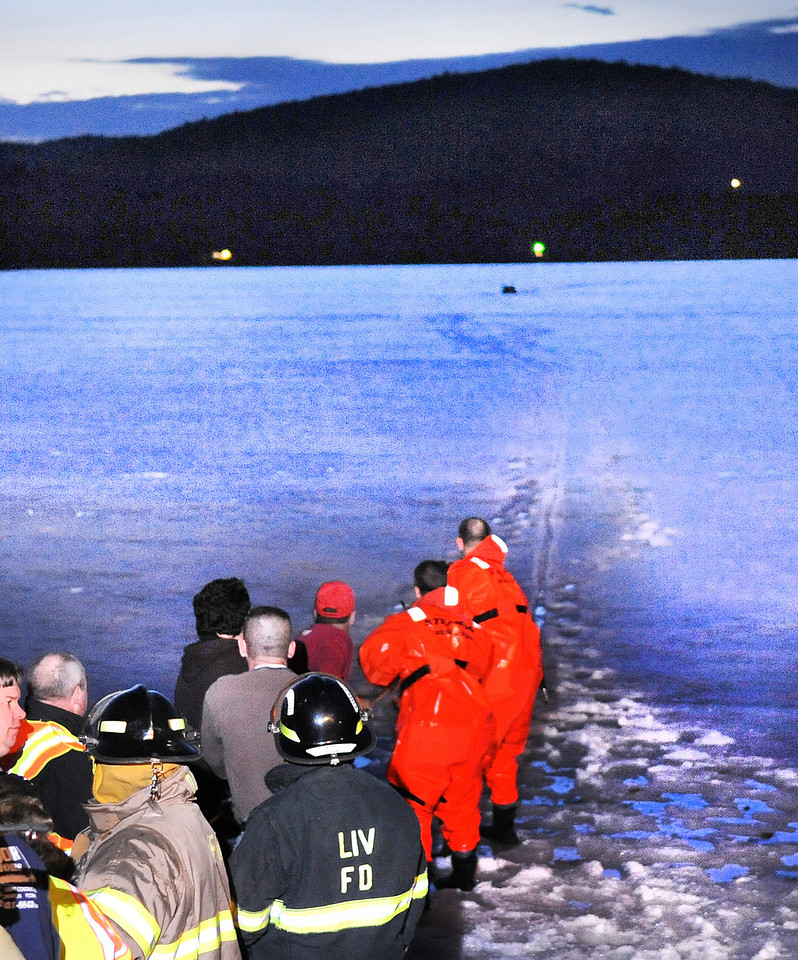 Area firefighters and residents work together to pull a line attached to a canoe Turner Fire and Rescue and a rescue craft Auburn Fire and Rescue used to rescue John Dudley after he fell through the ice on Bear Pond in Turner while cross country skiing across the pond.