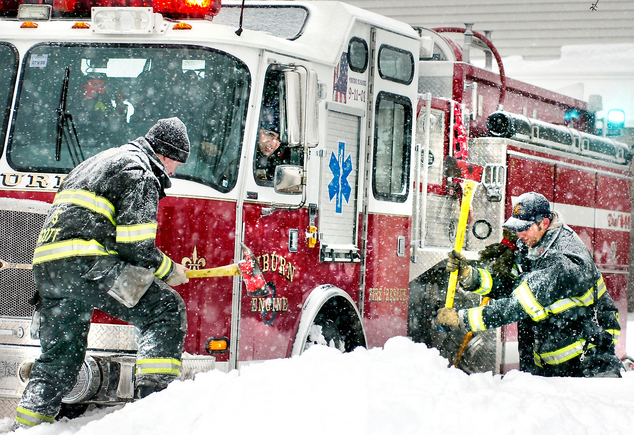 Auburn firefighters use their axes to help chop away a snowbank after their truck got stuck in the parking lot of the Auburn Plaza during the height of a snowstorm.  Nearly every truck responding to a gas leak got stuck in the icy lot.  A snowblower hit a natural gas pipe behind one of the stores forcing the majority of stores in the mall to be evacuated.