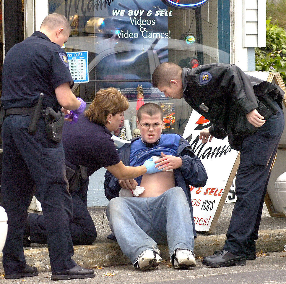 Lewiston police officers attend to stabbing victim in front of DVD Mania on Sabattus Street in Lewiston after he stumbled into the store to call for help after he was stabbed nearby.