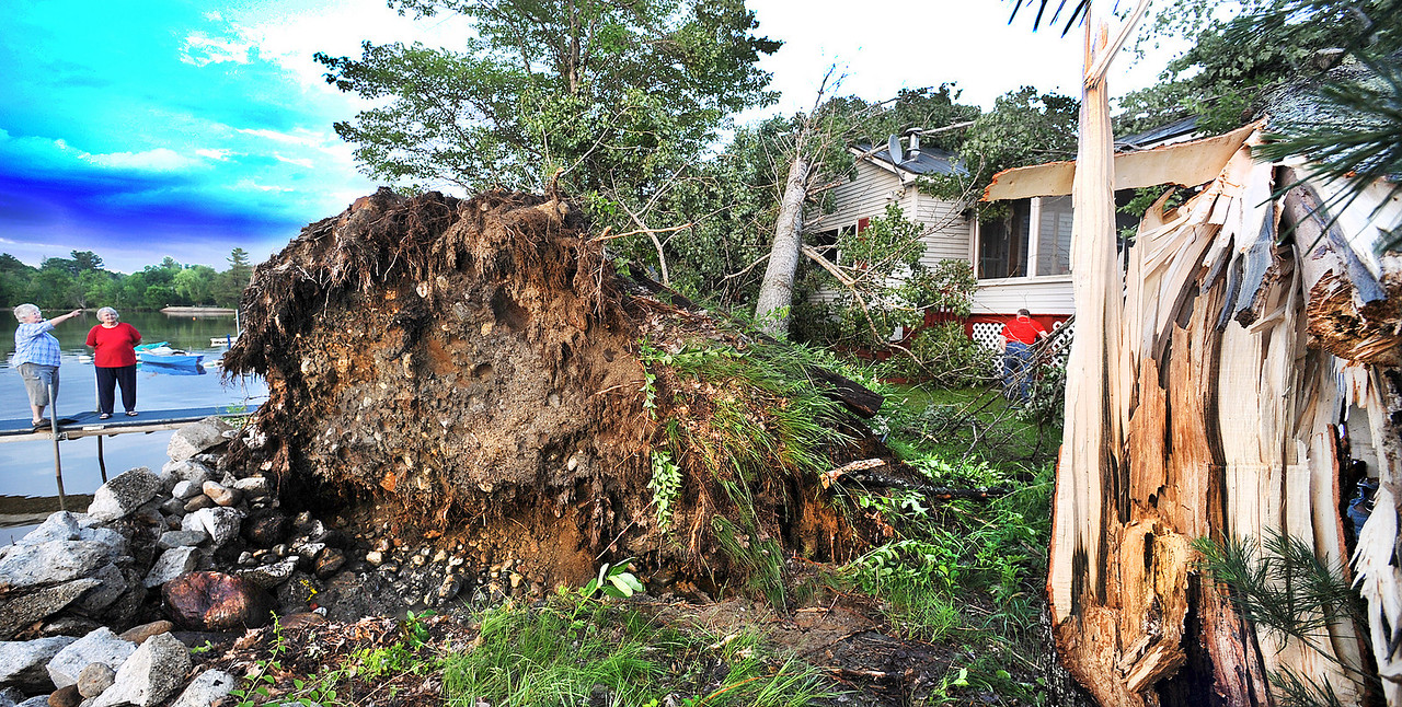 Ed Gray, center, picks up debris outside his home on 153 Chicoine Avenue in Auburn after a tornado uprooted several trees on the shore of Taylor Pond.  At left, Rachel Barcelou stands on the dock of her home while explaining to her sister in law, Germaine Bolduc, how it sounded like a train rushing past just before the trees came crashing down.