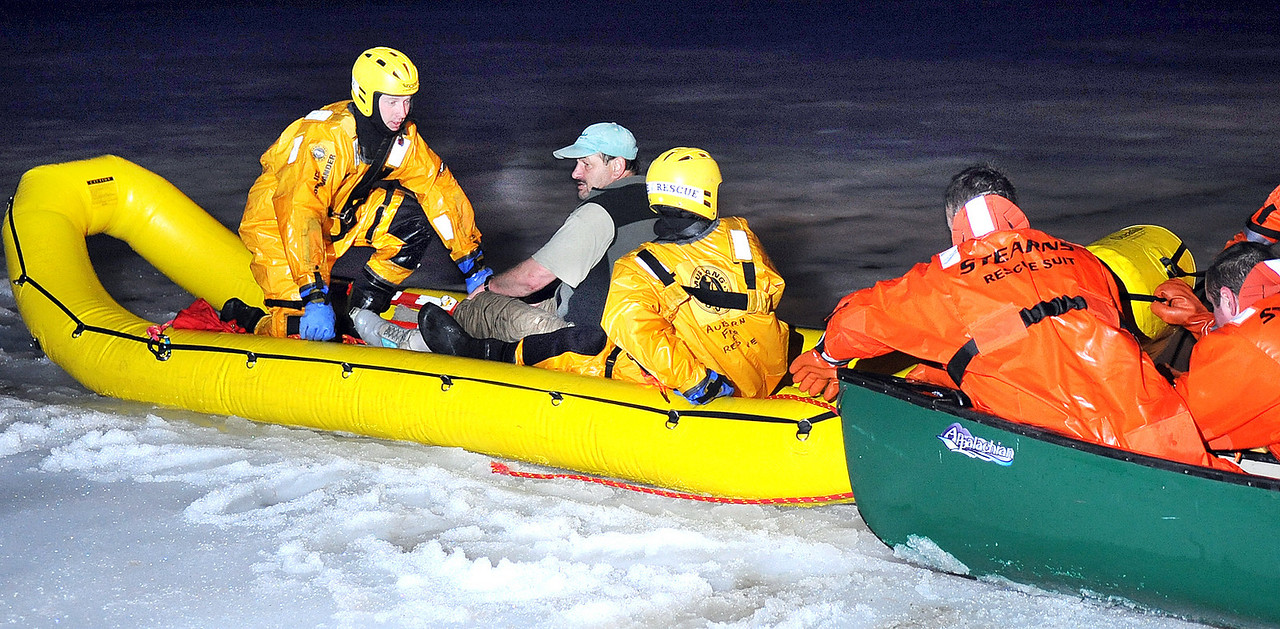 Auburn, left in yellow, and Turner, right in orange, fire and rescue personel are pulled to shore with John Dudley, center, after he fell through the ice on Bear Pond in Turner while cross country skiing across the pond.
