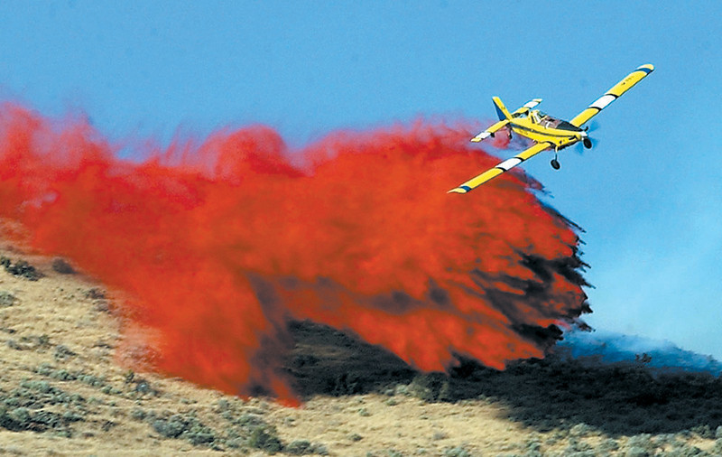Journal photo by Bill Schaefer<br /> A single-engine air tanker drops flame retardant in the Black Rock canyon area Wednesday afternoon. The fire had consumed over 1,000 acres. Origin of the fire is under investigation.