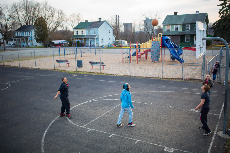 From left, Chris Bartuch, John Moccaldi, Jimmy Hughes, Ryan Lee, 10, and Merari Lopez, all of Ronco, watch Bartuch's shot sail toward the basket in the Ronco community park.  Lopez says they gather there almost every day to play basketball, weather permitting.  The Hatfield's Ferry Power Station lies dormant across the river, having closed in 2013, more than half a century after the Ronco mines closed in 1955.