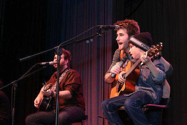 """Honorary 'third Swon Brother' John Roberts, 13, of Checotah sings """"Okie From Muskogee"""" with Zach, left, and Colton Swon. The Swons presented John with the signed guitar he played onstage. The guitar had been donated by John Michael's Music."""