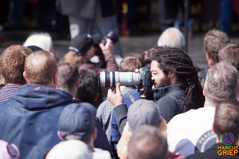 A photographer hides in among the crowd, snapping photos of the tea party attendees.