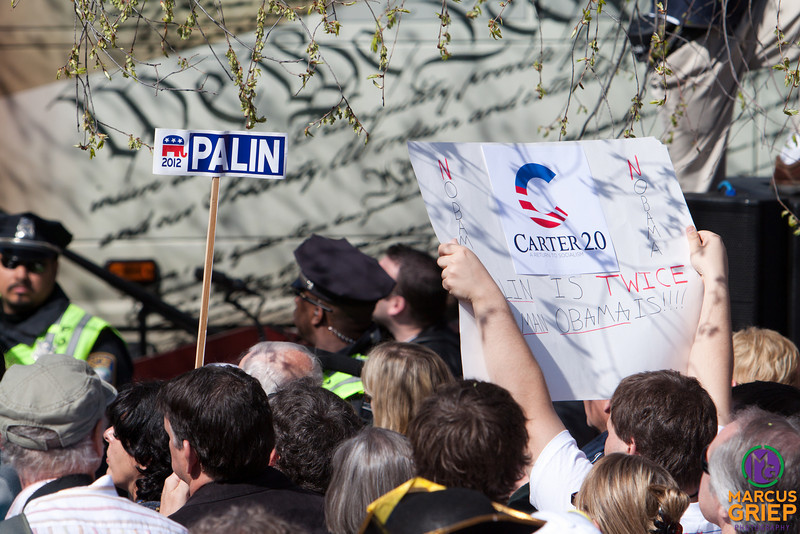 """An unofficial campaign sign is hoisted supporting a possible presidential bit by Sarah Palin in 2012. Next to it is a banner declaring the Obama presidency to be """"Carter 2.0"""". In the background is the image of the Constitution used as a skin for the Tea Party Express bus."""