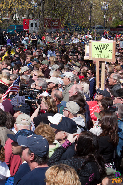 People stand shoulder-to-shoulder to listen to Sarah Palin speak, some carrying signs and flags, others attempting to capture the moment with a camera.