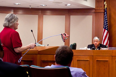 """At the hearing, some dog breeders like Sara Whittington oppose the bill.  They think existing animal cruelty statutes  should be enforced instead. Sara shows an empty harness, saying """"In ten years, these will be our dogs""""."""