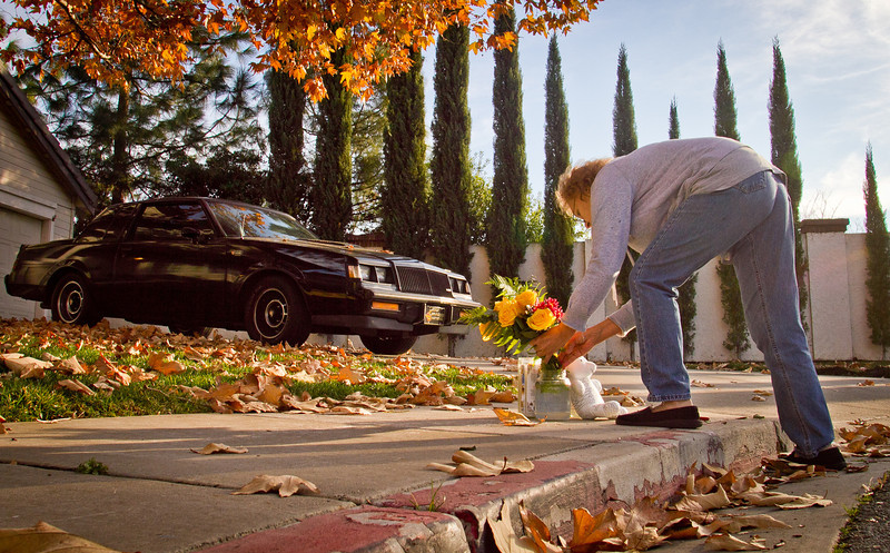 Lidia Vides puts flowers in a vase at a memorial for a 2 year old boy that was run over by a truck near his home in Antioch, Calif., on Tuesday, December 27, 2011.