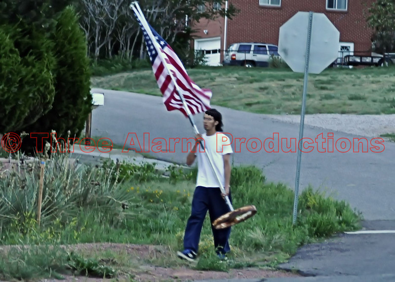 A citizen placing an American Flag near the intersection of the crash.