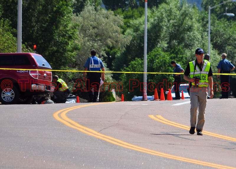 A Police Officer taking pictures of the scene at the site of the traffic accident.