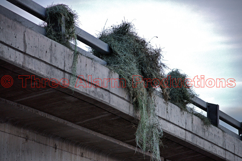 Damaged hay bales dangling off the side of the bridge on Interstate 25 near Bijou Street in Colorado Springs. This was the result of a tractor trailer rolling over onto a vehicle, while trying to negotiate a sharp curve on the highway.