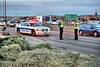 Colorado Springs Police Officers take charge of controlling traffic flow around the accident, involving a tractor trailer that was fully loaded with large hay bales. Hay can be seen in the foreground, which separated from the huge bales, some of it was strewn all over portions of the roadway on Interstate 25 in Colorado Springs, Colorado, USA.