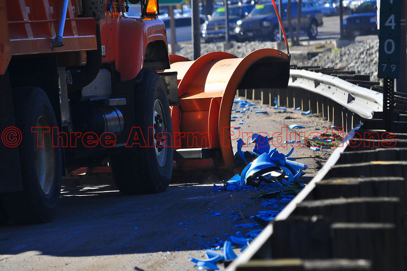 A CDOT snow plow cleans debris off of Interstate 25, after a semi-truck rolled over and lost it's load.