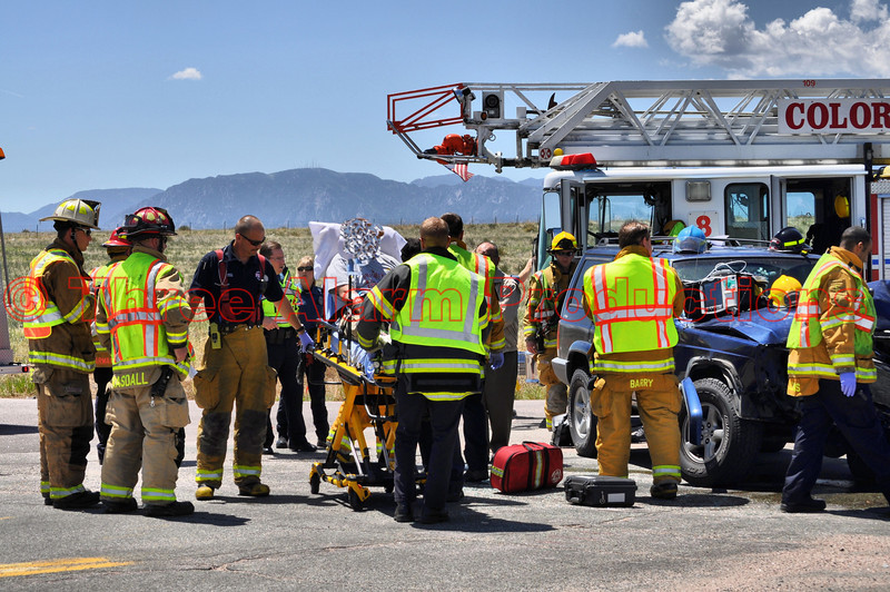 Fire crews from Colorado Springs Fire Department and Cimarron Hills Fire Department work the scene of a traffic accident involving an armored vehicle.