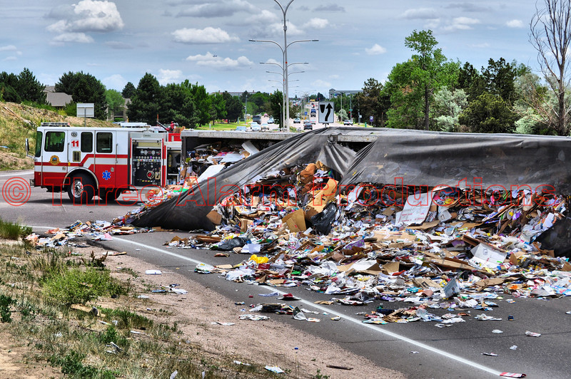 Trash was scattered all over Fountain Boulevard after a tractor trailer rolled onto its' side after colliding with a car in Colorado Springs, Colorado. Colorado Springs Fire Department's Engine 11 in the background.