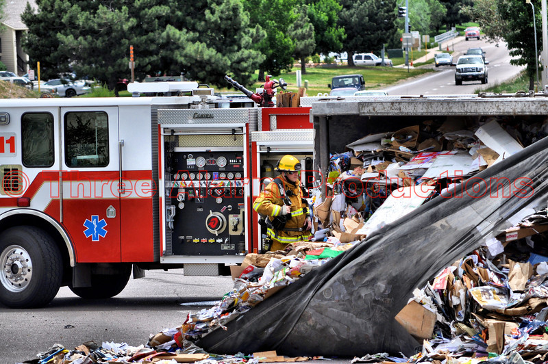 A Colorado Springs Fire Fighter examining a scattered load from a tractor trailer involved in collision at Fountain Boulevard and Academy Park Loop. In the background is Colorado Springs Fire Department's Engine 11.