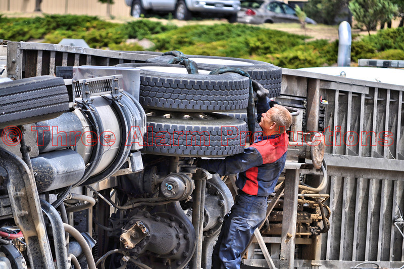 A worker with the towing company preparing to upright this tractor trailer involved in a collision in Colorado Springs, Colorado.<br /> <br /> On June 5, 2012 an accident occured involving a tractor trailer and a Nissan Altima. This took place at Fountain (24) and Academy Park Loop in Colorado Springs, Colorado. Extrication tools were used to cut and remove the roof of the car to get better access to the patient. The intersection was shut down for hours as crews worked to collect all the recycle type trash the truck was hauling. Three heavy duty tow trucks were called in to upright the truck from its' side.